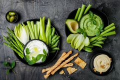 Green vegetables snack board with various dips. Yogurt sauce or labneh, hummus, herb hummus or pesto with crackers, grissini bread royalty free stock photography