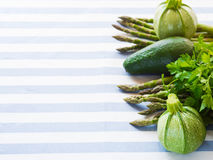 Green vegetables on table cloth. Green vegetables on striped table cloth Royalty Free Stock Photo