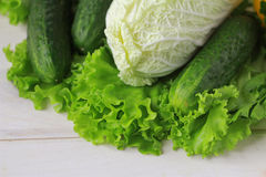 Green vegetables on wooden surface. A close up of cucumber, lettuce and cabbage on a wooden surface Stock Photography