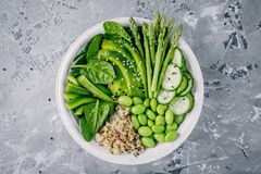 Green vegetarian buddha bowl salad with fresh vegetables and quinoa, spinach, avocado, asparagus, cucumber, edamame beans. Healthy green vegetarian buddha bowl royalty free stock image