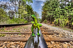 Green Velociraptor dinosaur walking on rail railroad tracks Stock Photo