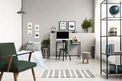 Green vintage armchair in stylish forest inspired teenager`s bedroom and workspace, copy space on empty wall. Green armchair in stylish forest inspired teenager` royalty free stock photography