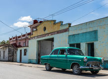 Green vintage car parked alone on the road in Cuba Royalty Free Stock Photos