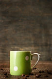 Green vintage ceramic cup at the wooden background Royalty Free Stock Image