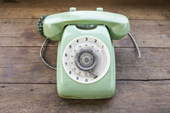 Green vintage telephone. On brown wood desk background Stock Photo