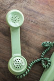Green vintage telephone. On brown wood desk background Stock Photography