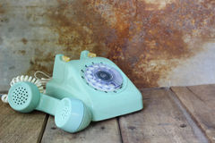 Green vintage telephone on wooden table Royalty Free Stock Photography