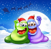 A green and a violet monster wearing a red hat for christmas Royalty Free Stock Images