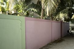 Green and violet wall in a maldivian village stock photography