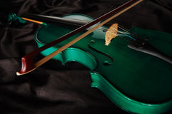 Green violin. And a bow on black silk royalty free stock photos