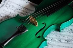 Green violin. And musical score stock photos