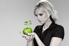 Green Vision. Woman holding the earth with plant over a neutral background Royalty Free Stock Image