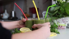 Green vitamin cocktail. Detox. A man takes to the kitchen table with three glasses of vitamin green cocktail with bananas, lemon and parsley stock video footage