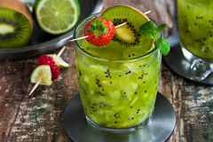 Green vodka, kiwi and lime cocktail. On wooden table stock photography