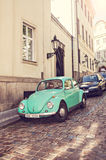 Green Volkswagen beetle on the street. Green Volkswagen Beetle car parked on the street of Prague, Czech Republic - vintage style Stock Photography