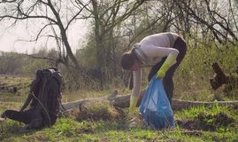 Green volunteer collecting garbage in the forest. Woman green volunteer collecting garbage in the forest. Eco friendly concept royalty free stock photography