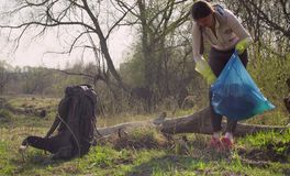 Green volunteer collecting garbage in the forest. Woman green volunteer collecting garbage in the forest. Eco friendly concept royalty free stock images