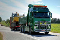 Green Volvo FH Hauls Tracked Excavator along Highway at Summer royalty free stock image