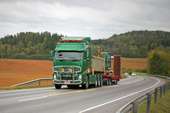Green Volvo FH Hauls Yanmar Mini Excavator Royalty Free Stock Photography