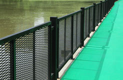 Green walkway with metal fence Royalty Free Stock Images