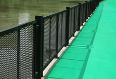 Green walkway with metal fence Royalty Free Stock Photos