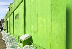 Green wall. Green textured, grungy wall with green reflection on the snow royalty free stock photography