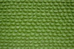 A green wall of oval cobble stones masonry. rough surface of the wall. pebble stone texture. Green wall of oval cobble stones masonry. rough surface of the wall stock photos