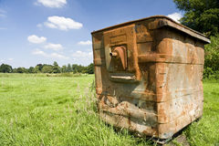 Green waste. Rusty old skip forgotten in a field royalty free stock photo