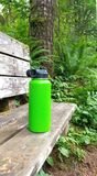 Green water bottle on bench. A green sports water bottle on a wooden bench in a forest royalty free stock images