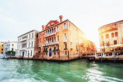 Green water channel with gondolas and colorful facades of old me Stock Photos