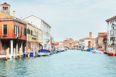 Green water channel with gondolas and colorful facades of old medieval buildings in the sun in Venice Royalty Free Stock Images