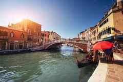 Green water channel with gondolas and colorful facades of old medieval buildings in the sun in Venice Royalty Free Stock Photography