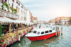 Green water channel with gondolas and colorful facades of old medieval buildings in the sun in Venice, Italy. Royalty Free Stock Photos