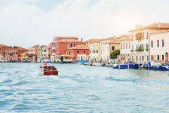 Green water channel with gondolas and colorful facades of old medieval buildings in the sun in Venice, Italy. Royalty Free Stock Photo
