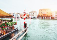 Green water channel with gondolas and colorful facades of old medieval buildings in the sun in Venice, Italy. Royalty Free Stock Images