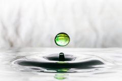 Green water drop bouncing. On water surface Royalty Free Stock Images