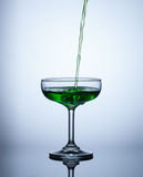Green water flows into the glass and makes bubbles. Object Royalty Free Stock Photo