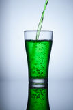 Green water flows into the glass and makes bubbles. Object Stock Photo