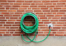Green water hose hanging red brick wall Royalty Free Stock Photography