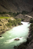Green water of the mountain river flowing through a valley among Royalty Free Stock Photos