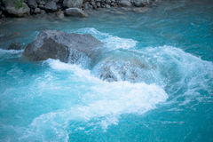 Green water of the mountain river and a large stone Royalty Free Stock Photos
