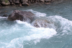 Green water of the mountain river and a large stone Stock Photography
