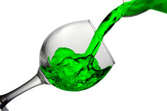 Green water pours into a glass on a white background Royalty Free Stock Photo