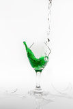 Green water spill from a broken wine glass on white background Stock Images