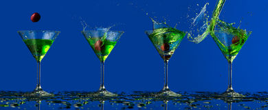 Green water splash in glass and cherry. Colored water splash in glass in blue background Stock Photo
