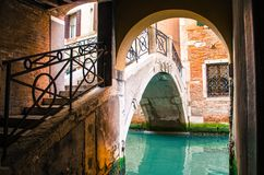 Green water under the bridge. Peaceful view of Venice, old area, old walls, bridge and canal royalty free stock image