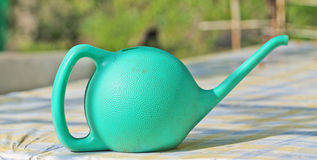 Green watering can. On pattern table stock photography