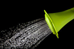 Green watering can pouring water with high speed shutter isolate Stock Images