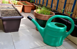 Green watering can and seedlings in flower boxes as a part of urban garden on the balcony Royalty Free Stock Images