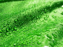 Green waterproof fabric with waterdrops close up stock photography